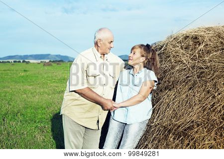 happy smiling couple: sixty eight year old man and sixty five year old woman isolated against blue background