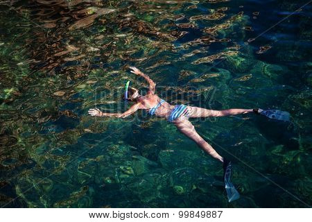 Young woman snorkeling in tropical lagoon