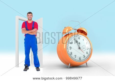 Handyman in overalls standing arms crossed over white backgound against alarm clock counting down to twelve