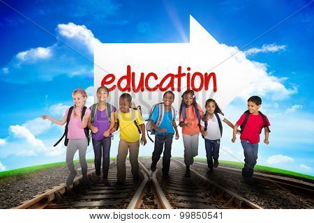 The word education and elementary pupils running against railway leading to blue sky