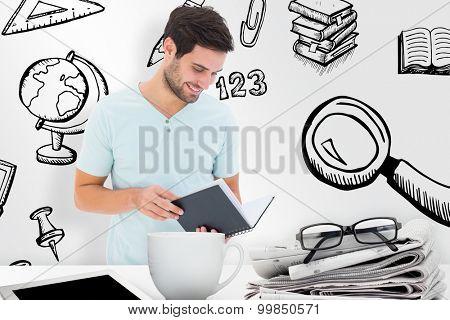 Student reading book against desk