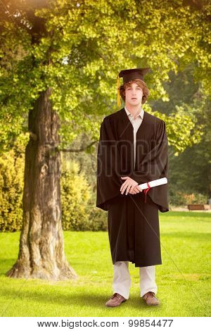 Student in graduate robe against trees and meadow