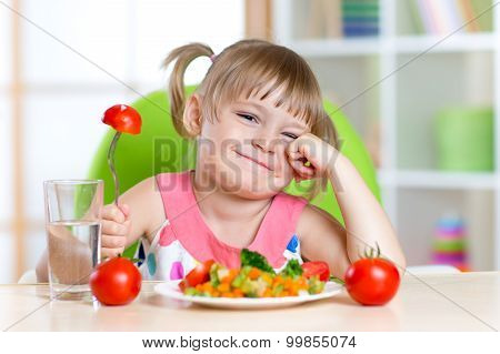 Little girl with expression of disgust against tomato
