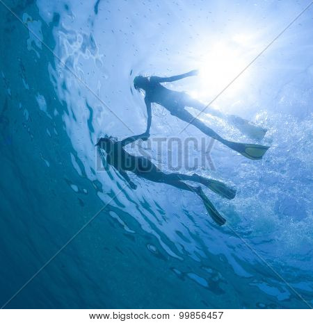 Underwater view of the couple snorkeling in the tropical sea