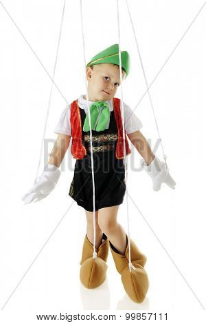 An adorable preschool Pinocchio marionette in a standing pose, strings and all.  On a white background.