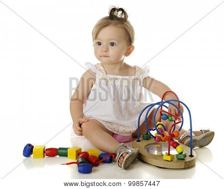 An adorable baby girl looking up from playing with colorful beads.  On a white background,