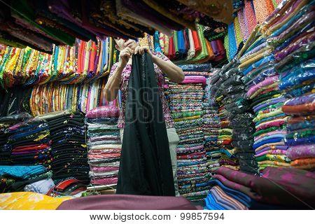 Vietnamese woman selling fabric at Ban Tanh central market