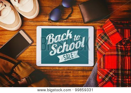 Back to school sale message against tablet shirt jean shoes smartphone wallet and bag