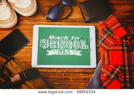 Back to school deals message against tablet shirt jean shoes smartphone wallet and bag