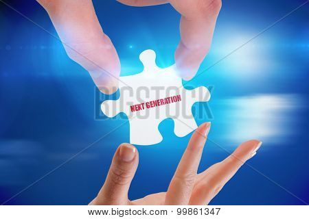 The word next generation and hands holding jigsaw against bright blue sky with clouds