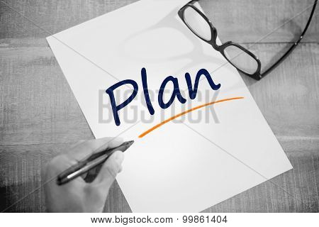 The word plan against left hand writing on white page on working desk