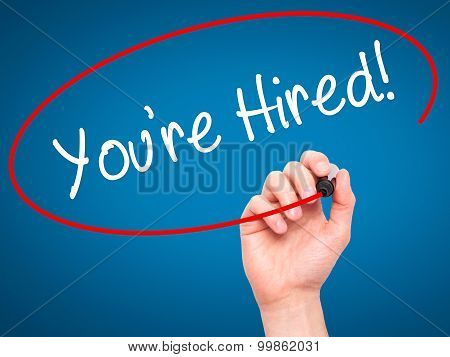 Man Hand writing You're Hired! with black marker on visual screen.