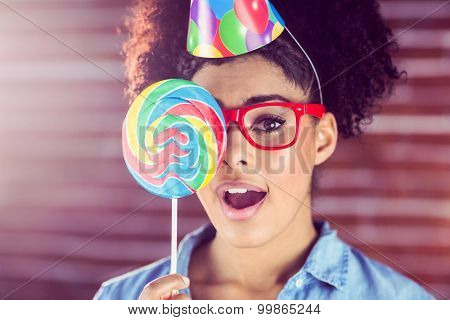 Surprised young woman holding a lollipop against her face on a re brick wall