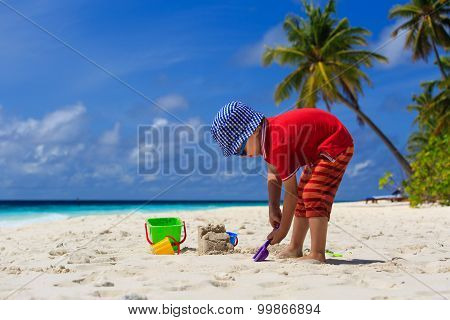 child building sandcastle on the beach