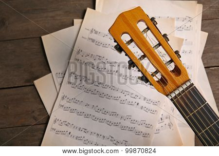 Music recording scene with guitar and music sheets on wooden table, closeup
