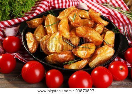 Baked potato wedges on checkered napkin, closeup