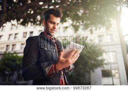 handsome man in down town los angeles using tablet on the go