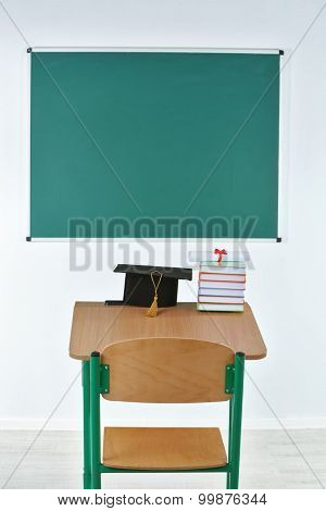School desk with master hat, stack of books and diploma in classroom