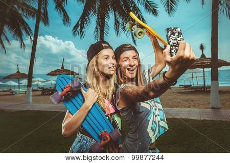 Two happy teenage girlfriends taking a selfie with smartphone outdoors on sunny summer day