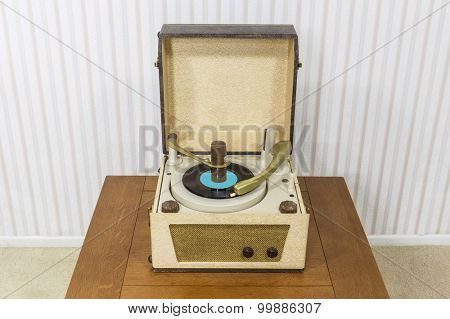 Old box style record player in table.