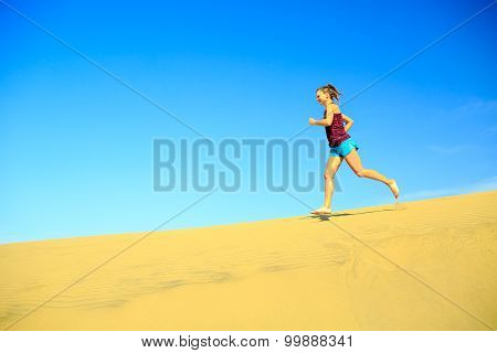 Young Woman Jogging Barefoot On Sand Desert Dunes