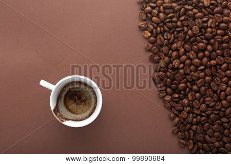 Cup of drunk coffee on brown background with beans