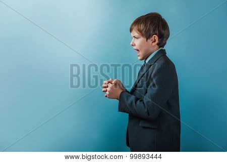a boy of twelve European appearance in a suit clenched fists ope
