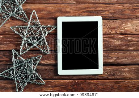 White tablet computer on a wooden background with Christmas stars