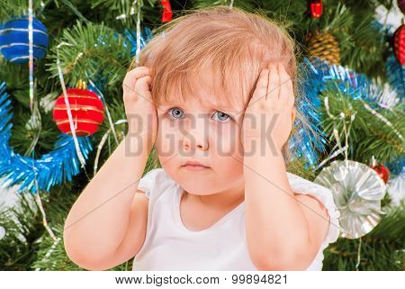 Upset and distraught little girl near the Christmas tree