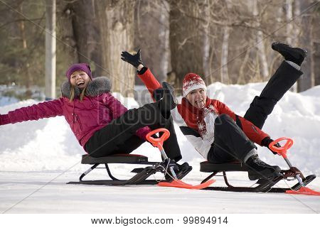 Two Young Girls On Little Snowmobiles Having Fun In Wintry Park