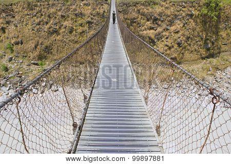 Long Foot Bridge With Walking Woman, Bridge Over Mountain River, Trek To Pokhara, Nepal