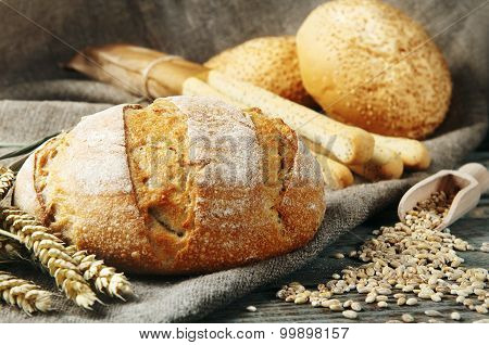 Loaf Of Bread On Sackcloth With Spikelets Of Wheat On The Wooden Table Closeup