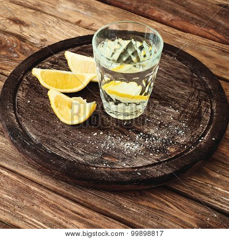 Glass Of Tequila With Lemon Slices On A Wooden Background