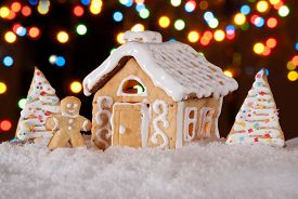 image of gingerbread man  - Gingerbread house with gingerbread man and christmas trees - JPG
