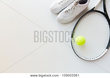 sport, fitness, healthy lifestyle and objects concept - close up of tennis racket with ball and sneakers
