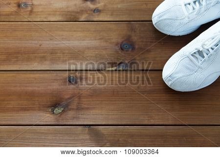 sport, fitness, shoes, footwear and objects concept - close up of sneakers on wooden floor