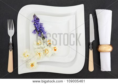 Elegant place setting with white porcelain dishes, antique cutlery, spring bluebell and narcissus flowers with napkin and ring over slate background.