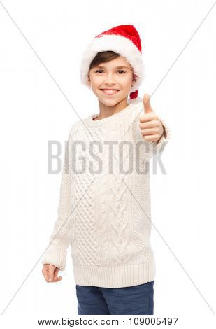 holidays, gesture, christmas, childhood and people concept - smiling happy boy in santa hat showing thumbs up