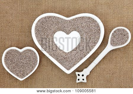 Chia seed health food in heart shaped porcelain bowls and spoon over hessian background. Salvia hispanica.