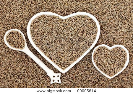 Rye grain in heart shaped bowls and porcelain spoon forming an abstract background.