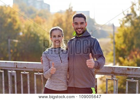 fitness, sport, people, gesture and lifestyle concept - smiling couple outdoors showing thumbs up at city
