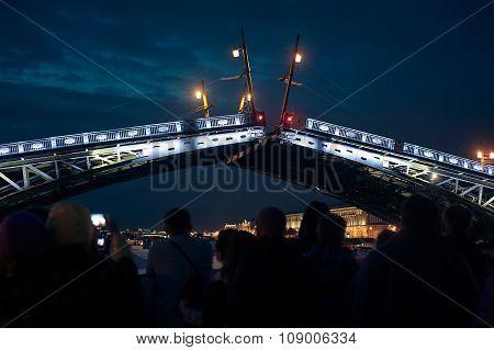 Night breeding bridge in St. Petersburg. Many people looking from ship under the bridge