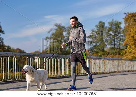 fitness, sport, people, pets and lifestyle concept - happy man with labrador retriever dog running outdoors