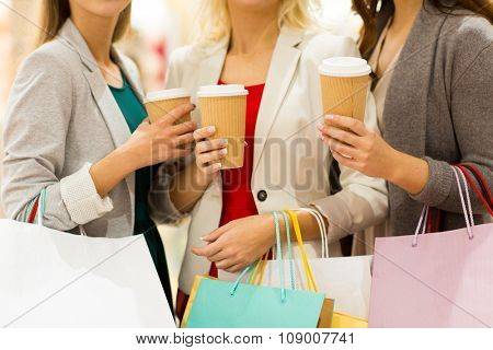 sale, drinks, consumerism and people concept - close up of women with shopping bags and coffee cups