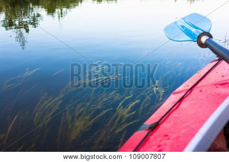 Blue paddle lying on kayak. Kayaking in a river