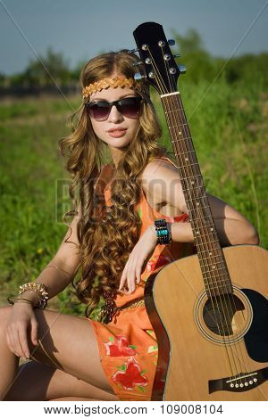 Young Hippie Girl On A Summer Field With Her Guitar