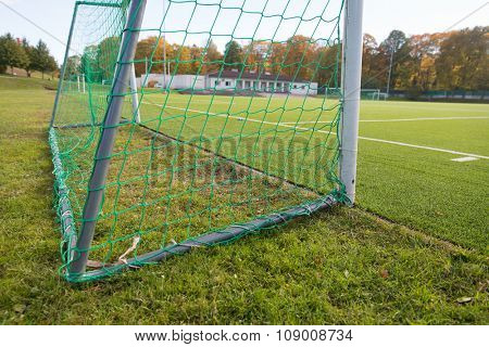 sport and equipment concept - close up of football goal on field