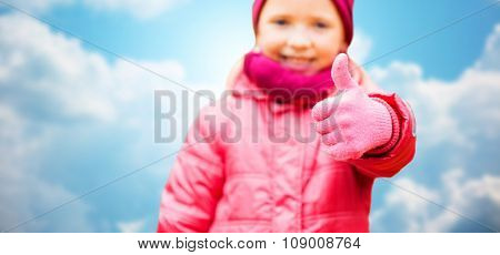 autumn, childhood, gesture and people concept - close up of happy little girl showing thumbs up outdoors over blue sky background