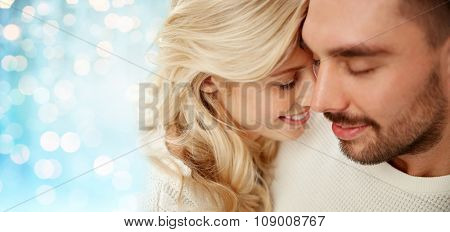 family, love, winter and people concept - close up of happy couple faces with closed eyes over blue holidays lights background