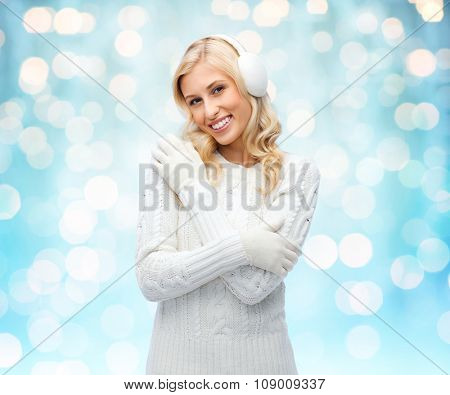 winter, fashion, christmas and people concept - smiling young woman in earmuffs and sweater over blue holidays lights background